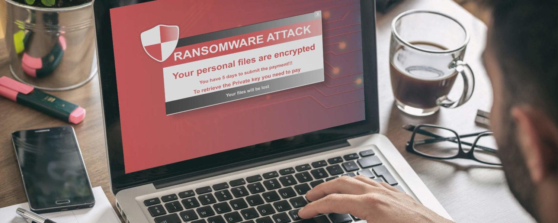 Mann am Laptop mit Viruswarnung auf dem Bildschirm - bildlich für Internetstrafrecht