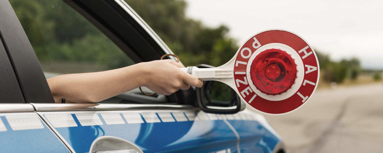 Polizeiauto mit Polizeikelle - bildlich für Ordnungswidrigkeiten im Verkehrsrecht