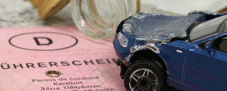 Führerschein und demoliertes Spielzeugauto - bildlich für Verkehrsstrafrecht